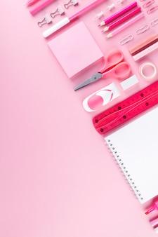 Varie forniture scolastiche e pittura su sfondo rosa. composizione geometrica e monocromatica. vista dall'alto. copia spazio