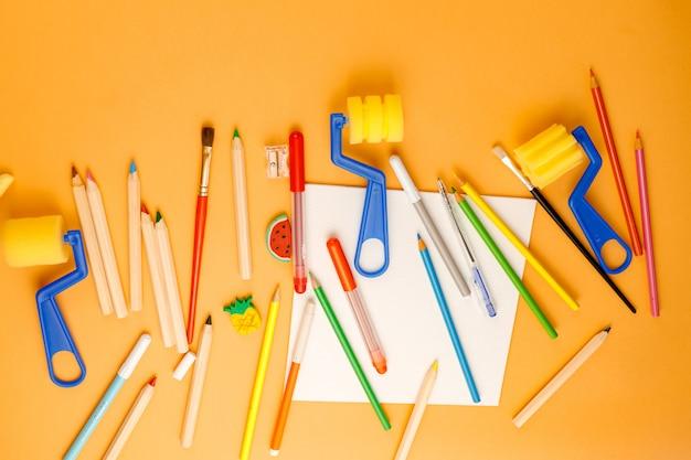 Vari materiali scolastici sulla superficie arancione