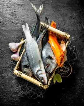 Vari pesci di mare sul vassoio con fette di aglio e lime. su sfondo nero rustico