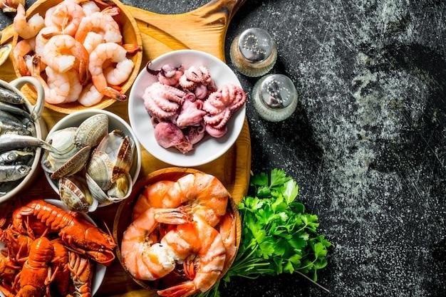 Vari frutti di mare su un tagliere rotondo con erbe e spezie.