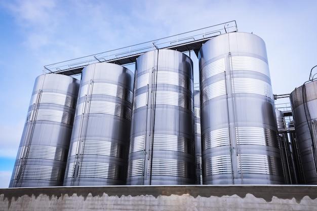 Vari silos e serbatoi alimentari metallici verticali per l'industria alimentare
