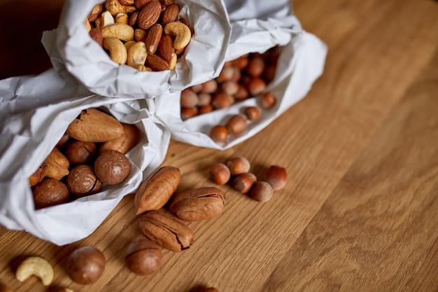 Vari tipi di noci sul tavolo in un sacchetto di carta