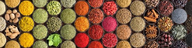 Varie spezie ed erbe come sfondo. condimenti colorati in tazze, vista dall'alto