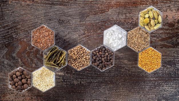 Varie spezie in vasi esagonali su una superficie di legno