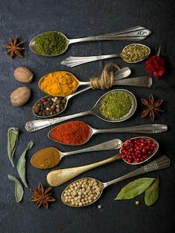Vari cucchiai di spezie sulla tavola nera. vista dall'alto con copia spazio