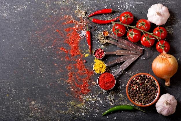 Varie spezie e verdure per cucinare sul tavolo scuro, vista dall'alto