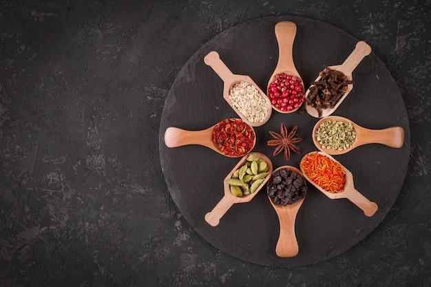 Varie spezie in cucchiai di legno sulla tavola di pietra scura.