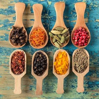 Varie spezie in cucchiai di legno su di legno.