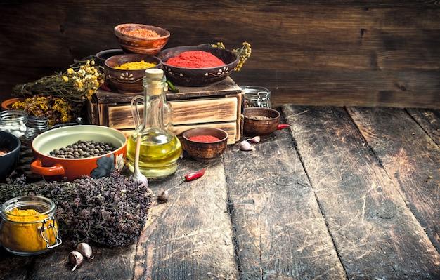 Varie spezie ed erbe aromatiche piccanti. su uno sfondo di legno.