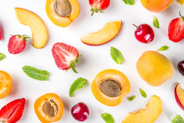 Vari frutti estivi e bacche su bianco, pattern flatlay