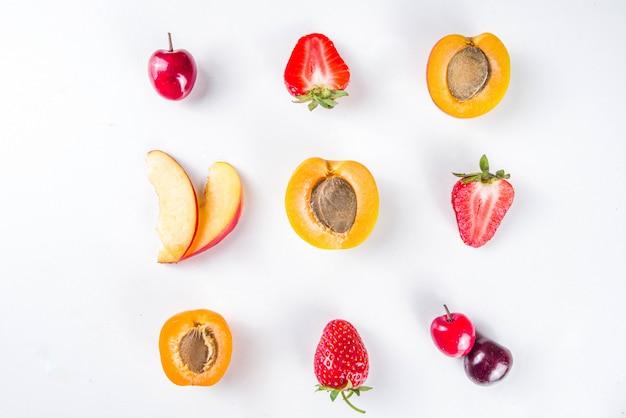 Vari frutti estivi e bacche su bianco, flatlay vista dall'alto