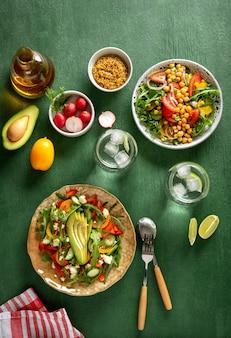 Varie insalate di verdure sane estive con avocado, cetriolo, ravanello, peperone e pomodoro su sfondo verde. cibo sano. vista dall'alto.