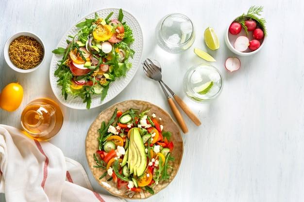 Varie insalate di verdure sane estive con avocado, cetriolo, ravanello, peperone e pomodoro. cibo sano. vista dall'alto.