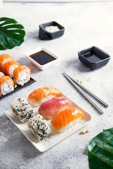 Vari sushi su piatto in ceramica con bastoncini coreani in metallo su superficie in pietra chiara con foglie verdi
