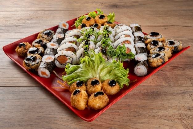 Vari sushi in zolla rossa sulla tavola di legno.