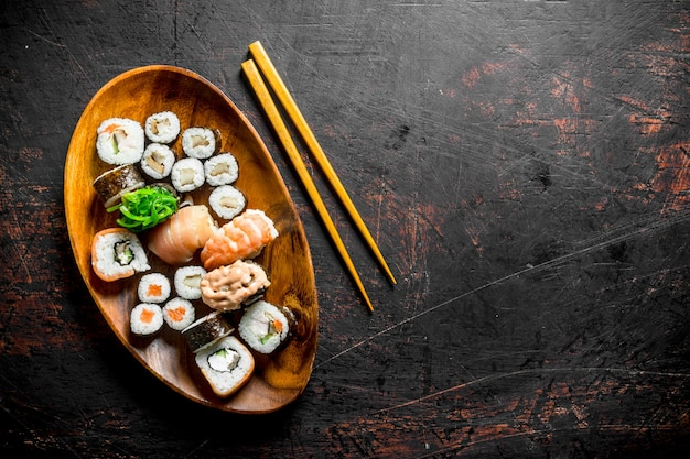 Vari sushi e panini su un piatto con bastoncini.