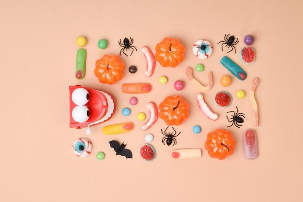 Vari dolci su uno sfondo arancione con un posto per il testo. sfondo per le vacanze di halloween. layout piatto, vista dall'alto, un posto da copiare.