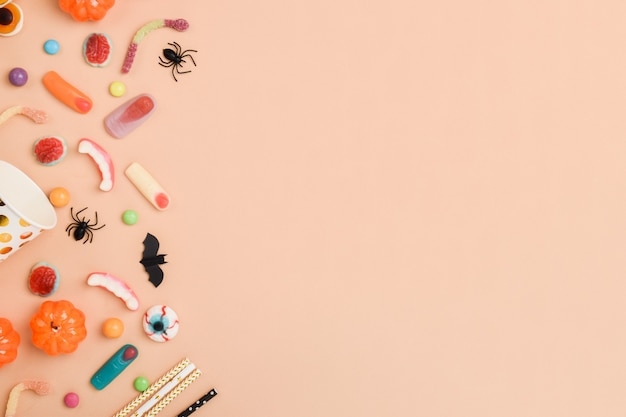 Vari dolci sull'arancia nella parte sinistra dello sfondo con spazio per il testo. sfondo per le vacanze di halloween. layout piatto, vista dall'alto, un posto da copiare.