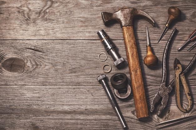 Vari strumenti per lavori di gioielleria su un tavolo di legno con spazio di copia