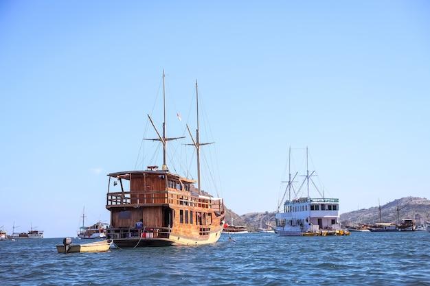 Varie barche di legno tradizionali che galleggiano sul mare vicino a un'isola a labuan bajo