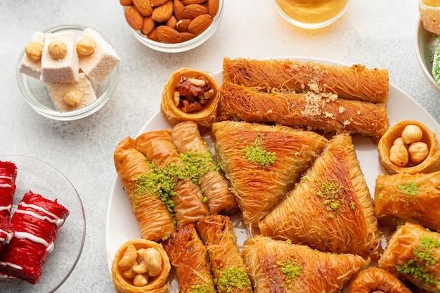 Vari dolci turchi e tazza di tè su sfondo bianco strutturato