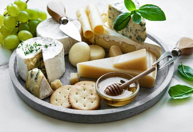 Vari tipi di formaggio, uva e miele su una superficie di marmo