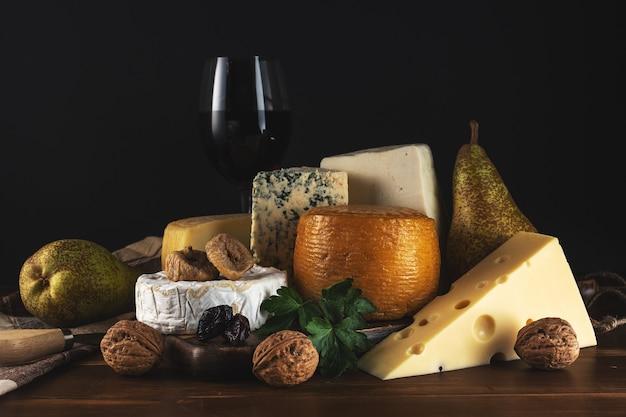 Vari tipi di formaggio con un bicchiere di vino sulla tavola in legno rustico.