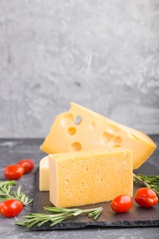 Vari tipi di formaggio con rosmarino e pomodori sul bordo di ardesia nera su un tavolo di cemento nero. vista laterale, primo piano, copia dello spazio.