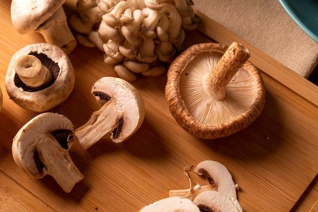 Vari tipi di funghi su un tavolo di legno.