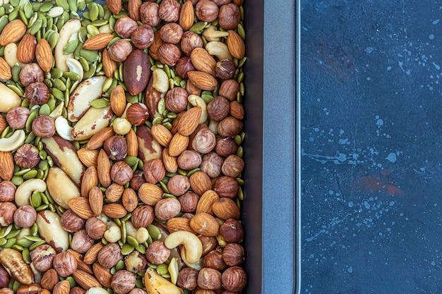 Vari tipi di noci sulla teglia. anacardi arrosto, nocciole, mandorle e noci del brasile