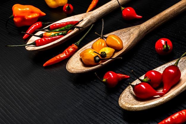 Vari tipi di peperoni peperoncini peperoncino bustina di peperone e pepe cumary di para¡ in cucchiai di legno su...