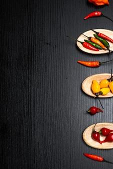 Vari tipi di peperoni su cucchiai di legno su fondo di legno rustico nero vista dall'alto spazio di copia