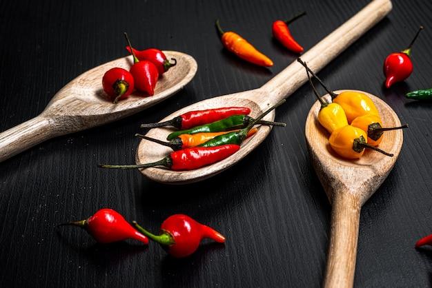 Vari tipi di peperoncino rosso e peperoncino dal brasile in cucchiai di legno