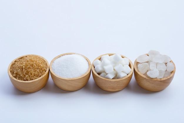 Vari tipi di zucchero su sfondo bianco.