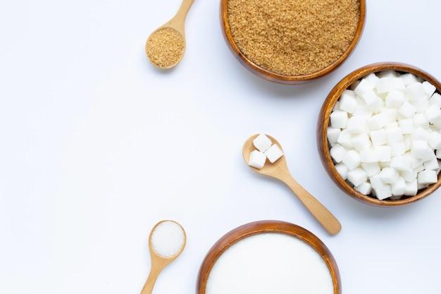 Vari tipi di zucchero su fondo bianco.