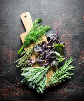 Vari tipi di erbe utili su un tagliere di legno sul tavolo rustico