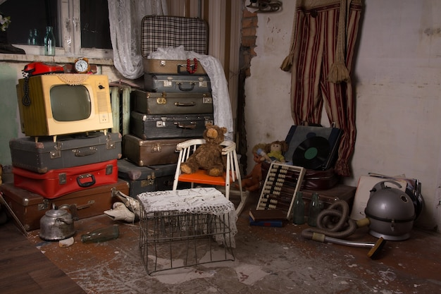 Vari vecchi oggetti inutilizzati come bagagli, televisione, gabbia, bollitore, aspirapolvere e tende in una stanza di una vecchia casa