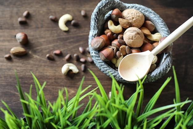 Varie noci utili e gustose su un tavolo di legno e pentole con erba verde