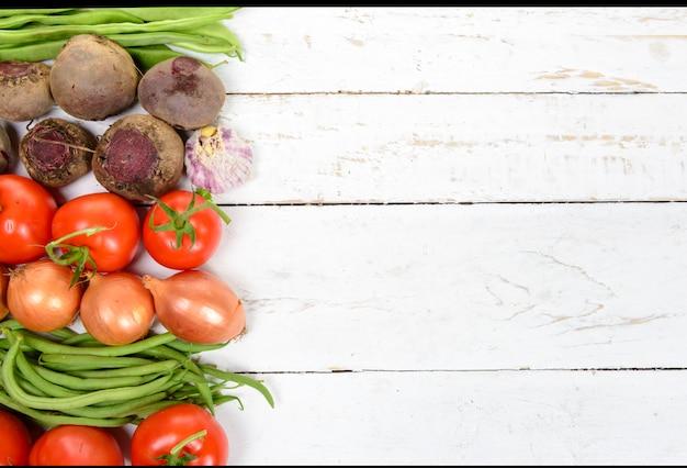 Varie verdure sul tavolo, barbabietole, pomodori, cipolle, aglio, fagiolini