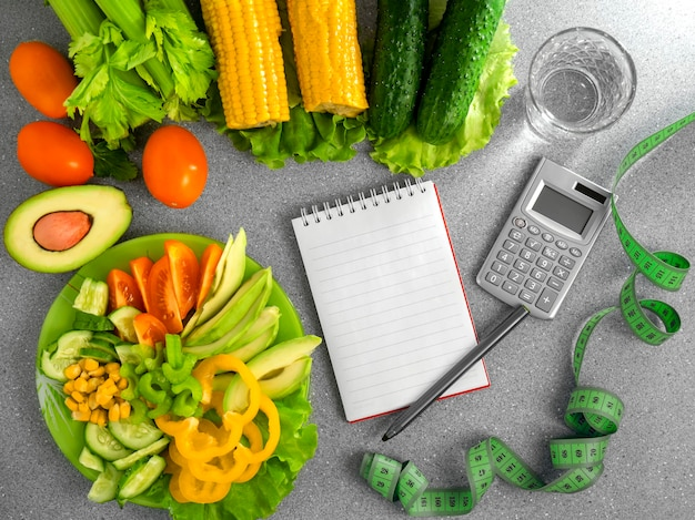 Varie verdure acqua e un quaderno sul tavolo dieta alimentare sana