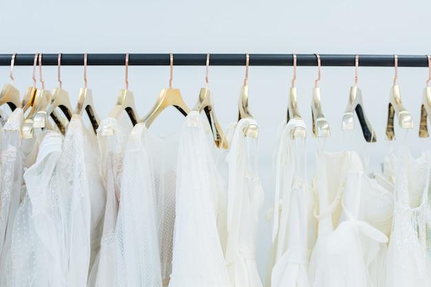 Vari abiti bianchi sui ganci appesi in fila sulla cremagliera nel negozio di abiti da sposa