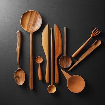 Vari utensili da cucina in legno su sfondo nero