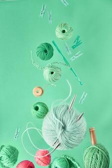 Vari filati di lana e ferri da maglia, fondo creativo di hobby tricottante sulla parete neo della menta