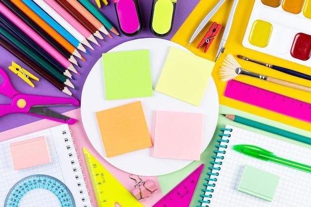 Vari strumenti di scrittura sulla superficie della carta colorata.