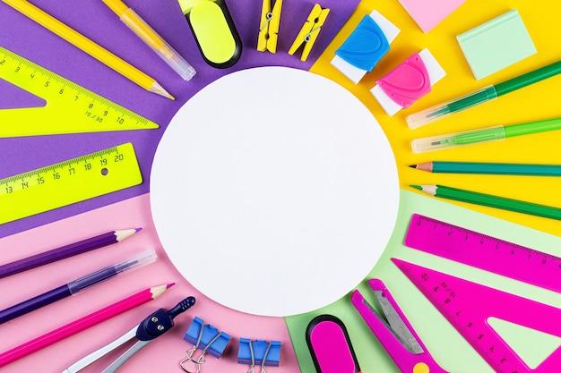 Vari strumenti di scrittura sulla superficie colorata.