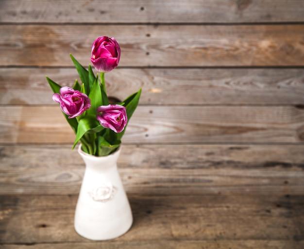 Vaso di tulipani naturali. fiori su uno sfondo di legno