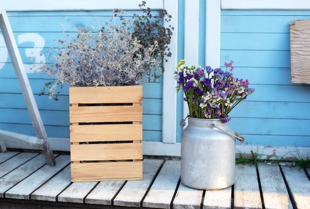 Vaso con fiori autunnali disposti sul patio. arredamento accogliente portico in legno della casa