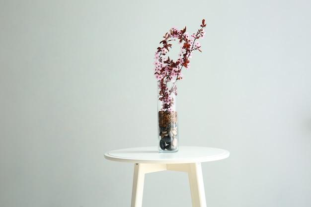 Vaso con bellissimi rami fioriti sul tavolo su sfondo chiaro