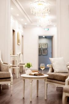 Un vaso con bellissimi fiori bianchi, un bicchiere di vino e pasticcini croccanti si trova sul tavolo in una stanza luminosa e accogliente. riprese all'interno