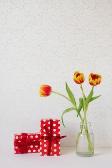 Vaso con un bouquet di bellissimi tulipani e scatole regalo sul tavolo.